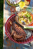A grilled beef steak with potato salad (top view)