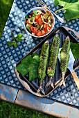 Gegrillte Makrelen in Feigenblättern mit Brotsalat auf Tisch im Freien