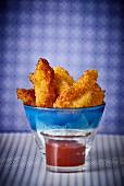 Chicken nuggets in a glass bowl with a tomato dip
