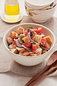 Tomato and bread salad with red onions and roasted pumpkin seeds