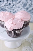 Three Chocolate Cupcakes with Pink Buttercream Frosting on a Cakestand
