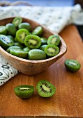 Kiwi berries (mini kiwi) in a wooden bowl on a rustic wooden surface