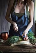 Frau schneidet Agretti (Salzkraut, Italien) mit Messer auf Holzschneidebrett