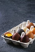 Brown and gray colored chicken Easter eggs in paper box with yolk over black concrete texture background