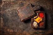 Verschiedene Gewürze in Vintage-Holzkiste auf braunem Untergrund (Aufsicht)