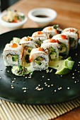Sushi with fish, avocado and fresh cheese on a black plate