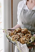 A woman is holding freshly baked parsnip morning glory muffins