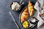 Breakfast with two croissant, butter, cottage cheese, cream, sliced mango fruit