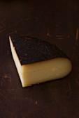 Ein Stück Käse auf braunem Holzuntergrund