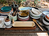 A collection of crockery on a wooden table outdoors