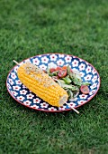 Marinated corn on the cob with tomato and asparagus salad