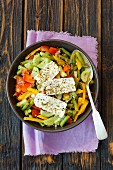 A colourful vegetable salad with fresh cheese