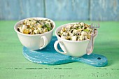 Potato salad with mayonnaise and pickled gherkins, served in two cups