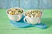 Kartoffelsalat mit Mayonnaise und Essiggurke in zwei Tassen