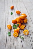 Fresh kumquats, whole and halved, on a wooden board