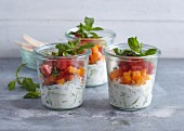 Layered salad with cucumber, orange pepper, tomatoes and Greek yoghurt