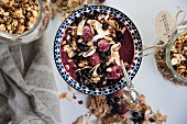 A smoothie bowl with granola, raspberries and blueberries