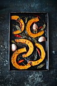 Oven-roasted pumpkin wedges with chilli and garlic (seen from above)