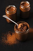 Chocolate mousse in small jars on a black slate