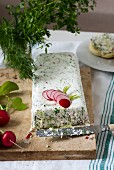 A big piece of quark cheese and herbs terrine on a marble board. Radishes, dill, parsley and a roll on a white plate in the background