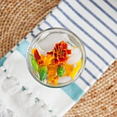 Mineral water in a glass infused with melon and edible flowers (top view)