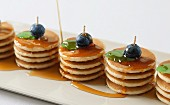 Several piles of mini pancakes with maple syrup, blueberries and mint