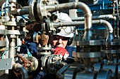 Worker checking pump on an oil and gas refinery