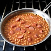 Frankfurters with baked beans in skillet