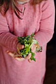 A young girl holding fresh lettuce leaves in her hand