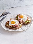 Two slices of bread topped with ham, fried egg and avocado
