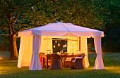 Abendstimmung mit elegantem, Pavillion, Korbmöbeln und Kerzenlichtern auf Sommerwiese