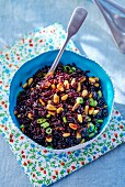 Rice salad with black rice, spring onion and pine nuts