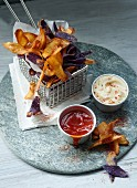 Colourful potato crisps with ketchup and chilli mayonnaise