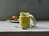 A glass jar of asparagus pesto, with green asparagus and ham in the background