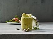 Ein Glas Spargelpesto, im Hintergrund grüner Spargel mit Schinken