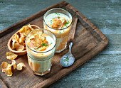Potato soup with potato crisps and chopped herbs