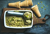 Homemade pistachio ice cream in ceramic mold with metal scooper, crashed pistachio nuts and waffle cones