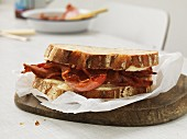 A sandwich with cheese and crispy bacon