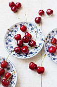 Fresh cherries on and around blue and white plates