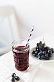 Red grape juice in a glass with a straw