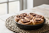 Cinnamon and cardomom buns in a pan on a kitchen table with window in the background