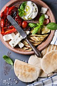 Ingredients for making pita bread sandwiches: grilled vegetables, basil and feta cheese