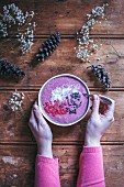 Woman eating raspberry smoothie bowl on a rustic wooden table
