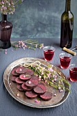 Marzipan Hibiscus Cups served on a copper tray with a dessert wine