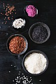 Variety assortment of raw uncooked colorful rice white, black, brown, pink in black bowls over wooden background