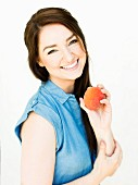 Woman wearing blue top holding peach