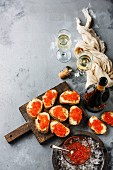 Sandwiches with salmon red caviar and champagne on concrete background