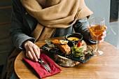 Frau isst gegrillten Lachs auf Wacholderzweigen im Restaurant