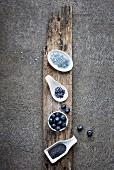 Blue food: blue salt, oolong blend tea, blueberries, poppy seeds on grey background
