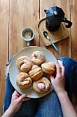 Frau isst Cruffin (Mischung aus Croissant und Muffin) zum Frühstückskaffee